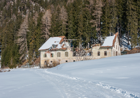 mountain house abandoned with damaged roof. winter season, snow around