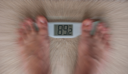 blur on weight scale and feet. focus on numbers Stock Photo