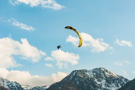paraglider flying in the blue sky