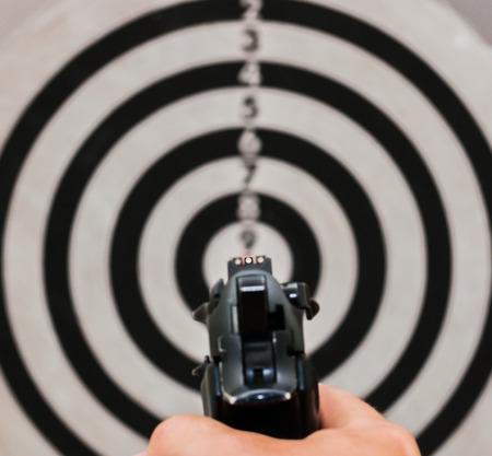 Shooting range, gun on target,  focus on front sight 版權商用圖片