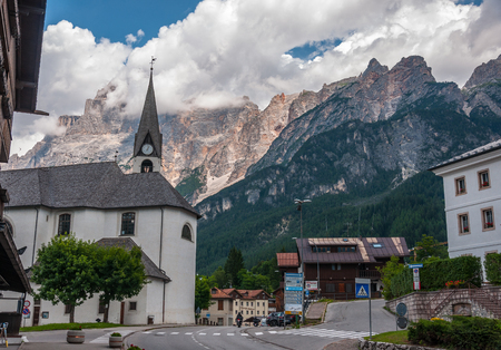 Summer view of Dolomites of Cortina dAmpezzo (BL) (Italy). Mountains, clouds, sky and church.