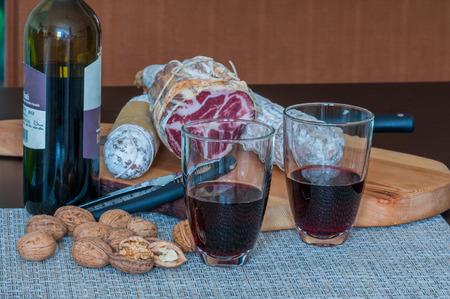 Indoor closeup of Italian red wine (Chianti), walnuts and salami 版權商用圖片