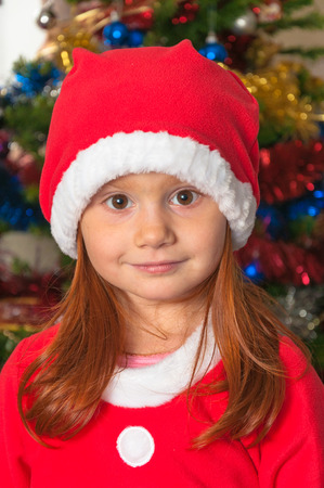 A little redhair girl dressed as Santa Claus, background Christmas decorations