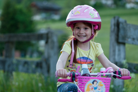 Little girl bicycling, background blurred,pink helmet Stock Photo