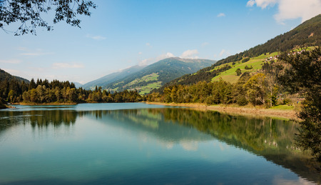 lake panorama on the alps, still water reflects the mountains and green trees