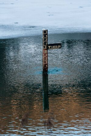 water depth measurement tool in mountains partially iced lake in Tyrol (Austria)