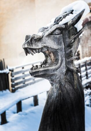 wooden sculpture depicting a dragon, mouth wide open, covered in snow Imagens