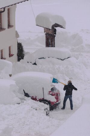 man shovels snow from his completely covered by snow