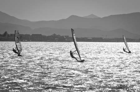 Three windsurfers and mountains