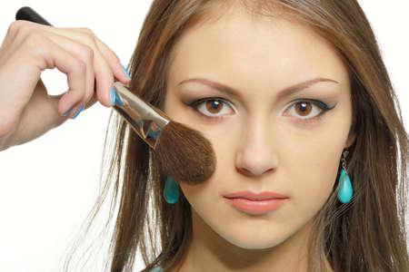 Mädchen tun Make-up. In ihren Händen hält sie einen Pinsel. Sie malt ihre Augen. Das Mädchen hat braune Augen und sie brbnetka. Portrait auf einem weißen Hintergrund in high key