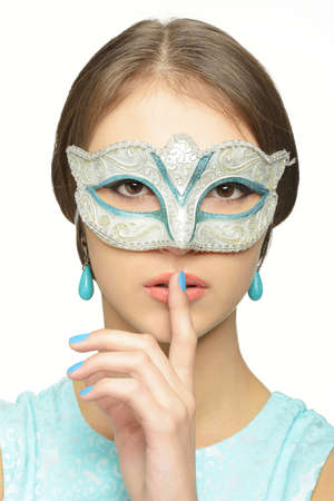 brown  eyed: Girl in carnival mask from Venice. The mask is placed over the face. A finger pressed to her lips. Brown eyes, azure makeup. Young brunette