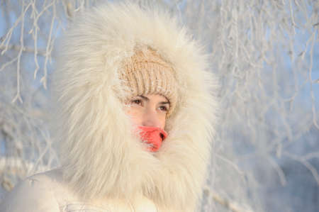 very cold: Girl with hoarfrost on the eyes. The white fur coat and hood. Very cold, frost. His face is closed, you can see only the eyes
