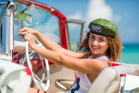 cabriolet: A young, curly girl is sitting in a while cabriolet on a tropical beach