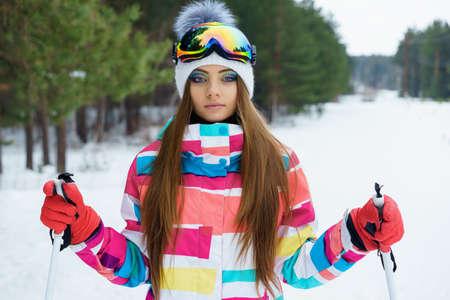 Une jeune fille avec des vêtements de maquillage et de sport lumineux détient des bâtons de ski sur une piste de ski