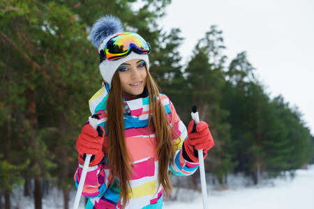 brigh: A young girl with a brigh makeup and sport clothes holds ski poles on a ski slope Stock Photo