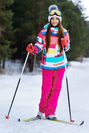 ski goggles: Young girl skiing in the winter woods. Bright make-up, clothes and ski goggles Stock Photo