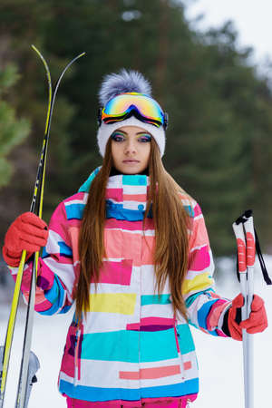 ski goggles: Girl in gear for skiing. Athlete skiing in the winter forest. Bright clothing, ski goggles and makeup