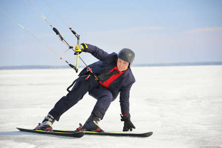 Male businessman in a classic suit. Skiing and controls the kite. Winter day and clean blue sky
