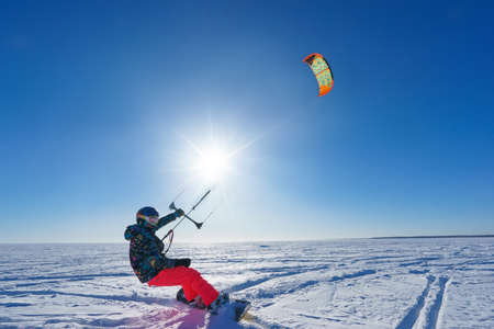 govern: Athlete in bright clothes riding in the snow on a snowboard and kite controls. Deep blue sky and sun in the background Stock Photo