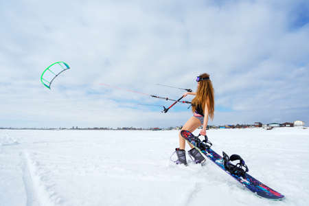 reckless: A slender girl in a bathing suit in the snow in the winter. Sportswoman snowboarding. Athlete runs a kite. Stock Photo