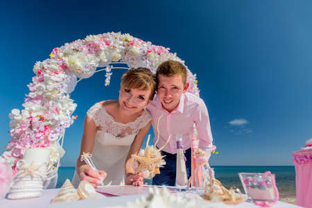 A beautiful couple at a wedding ceremony on a sunny beach