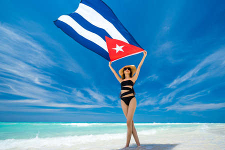 Beautiful young girl in black swimsuit is standing on the beach on the background of azure caribbean sea and holding a flag of Cuba in her arms. Hot summer day at the coastline of the Cuba.