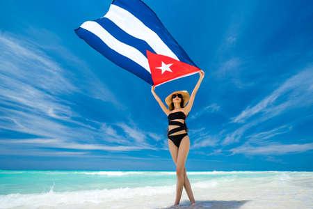 La chica joven hermosa en traje de baño negro se está colocando en la playa en el fondo del mar del Caribe azul y está sosteniendo una bandera de Cuba en sus brazos. Caluroso día de verano en la costa de Cuba