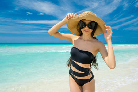Beautiful young girl in the straw hat, black swimsuit and sunglasses is smiling and standing on the beach on the background of azure caribbean sea. Hot summer day at the coastline of the Cuba. Stock Photo