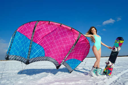 snowkiting: Beautiful girl in swimsuit is posing with a kite on the background of snow and blue serene sky