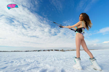 snowkiting: Beautiful girl in swimsuit is posing with a bright coloured kite on the background of snow and blue serene sky