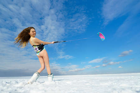 snowkiting: Young handsome woman in swimsuit is posing with a bright coloured kite on the background of snow and blue serene sky
