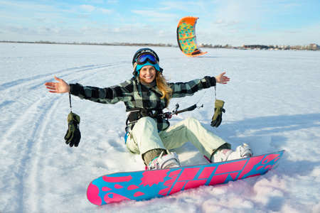snowkiting: Beautiful girl is siting on the snow with kite on her legs on the background of snow and blue sky Stock Photo