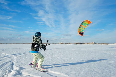 snowkiting: Beautiful young woman is kiting on the background of white snow and blue sky at sunny day