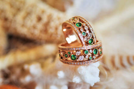 rite: Vintage wedding rings of gold, diamonds and emeralds. Lie on the scenery of starfish and seashells