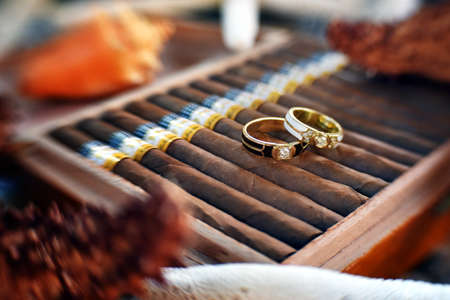 rite: Wedding rings are lying on the pack of cigars.