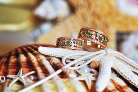 fidelidad: Vintage wedding rings of gold, diamonds and emeralds. Lie on the scenery of starfish and seashells