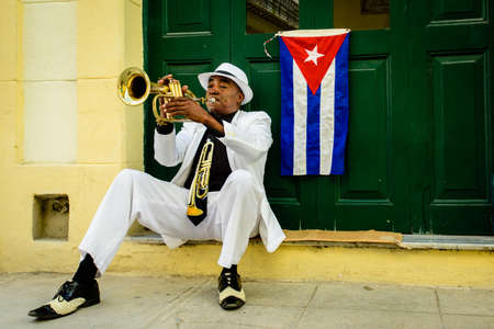 HAVANA, CUBA - MAY 17, 2016: Musician is playing saxophone in the street of Old Havana. Flag of Cuba is on the door. The colour of modern and ancient Cuba.