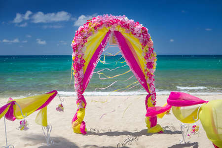 Accessory kit for a wedding is on the shores of the Caribbean Sea. Arch is decorated with curtains and flowers.