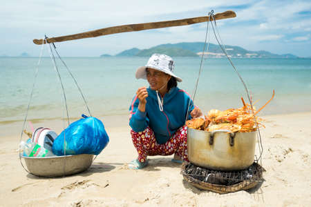 NHA TRANG, VIETNAM - JUNE 19, 2016: Merchant is selling lobsters to tourists on a beach on background of the sea and mountains in Vietnam Editorial