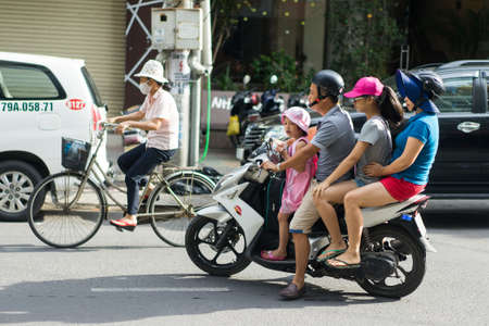 NHA TRANG, VIETNAM - JUNE 20, 2016: Mother, father and two daughters are riding the motorcycle on the street in the downtown of Vietnam