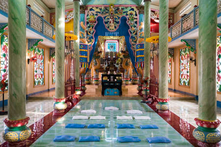 high altar: HO CHI MINH CITY, VIETNAM - JUNE 26, 2016: Interior of a Buddhist temple with high columns and bright colorful walls. Pillows for pray are laying down on the floor before an altar with Buddhist deity. Editorial