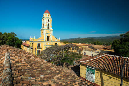 TRINIDAD, CUBA - FEBRUARY 25, 2014: Panoramic view to huge yellow ancient chapel, narrow streets, roofs of  local houses, central square and mountains with jungle behind at summer sunny day