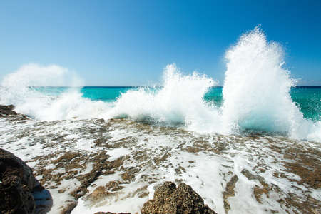 High waves of the Caribbean Sea are splashing hardly against rocks on a coastline at hot summer sunny day