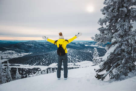 The young woman in a yellow jacket, white cap and with black backpack stands a back near fir-tree at top of the mountain, reaches hands for the sun and looks at the snow-covered valley