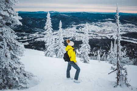 snowcovered: Young woman in yellow jacket, white cap with pompon and with black backpack stands sidewalk near fir-tree at top of the snow mountain and looks directly at the snow-covered valley Stock Photo