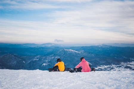 SHEREGESH, RUSIA - 7 DE DICIEMBRE DE 2016: Dos snowboarders de los deportistas en traje rosado anaranjado brillante se sientan y se preparan para la pendiente del top de la nieve de la montaña en un snowboard abajo. Vista panorámica a la estación de esquí en un fondo