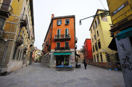 graffity: VENICE, ITALY - SEPTEMBER 15, 2015: The tourists are walking through the narrow streets of Venice. On empty street there are tables near the bar which is still closed. There is a bright colorful house in the middle. Editorial