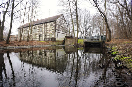 water mill: WUSTERHAUSEN, GERMANY - November 05, 2015: View to river, old water mill and houses on the shore in the middle of the forest on a cloudy day. Editorial