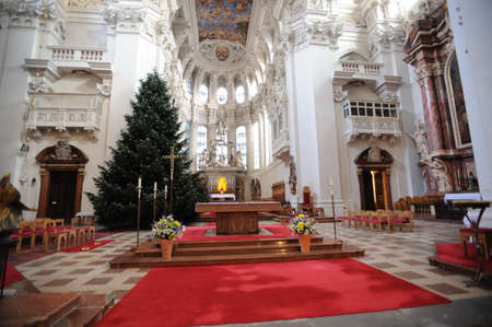 high altar: WUSTERHAUSEN, GERMANY - December 11, 2015: The interior of the empty church in Germany. There are red carpet on the floor, the altar in the middle of the hall, high ceiling with multi-coloured stained-glass window and huge Christmas tree.