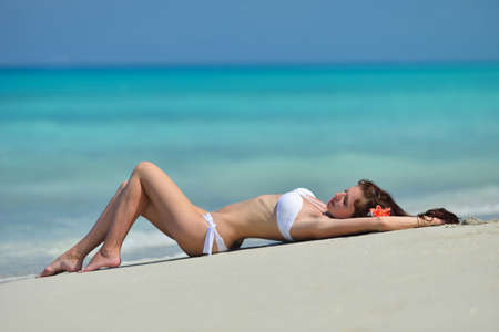 Beautiful pretty young girl with red flower in her long brown hair and white swimsuit is lying on the beach. Chrystal azure water of caribbean sea at coastline at summer sunny day.